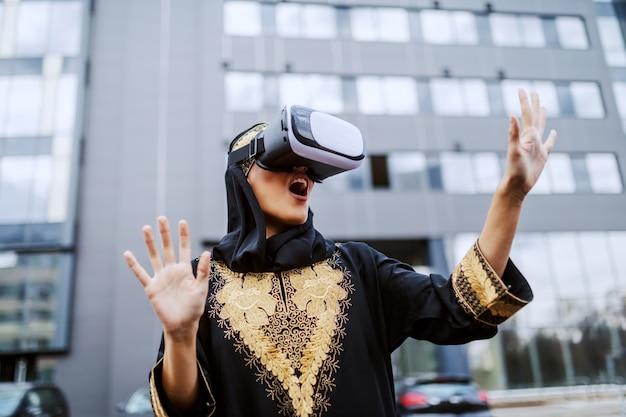 Attraente giovane donna musulmana stupita in abbigliamento tradizionale in piedi davanti all'edificio aziendale e utilizzando occhiali vr.