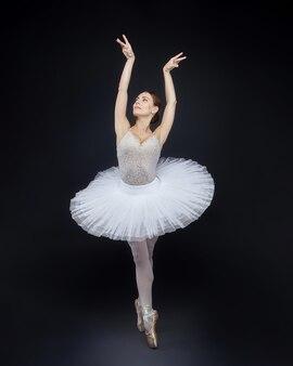 Attraente ballerina posa con grazia su uno sfondo nero