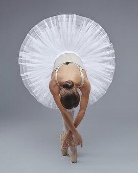Attraente ballerina posa con grazia su uno sfondo bianco