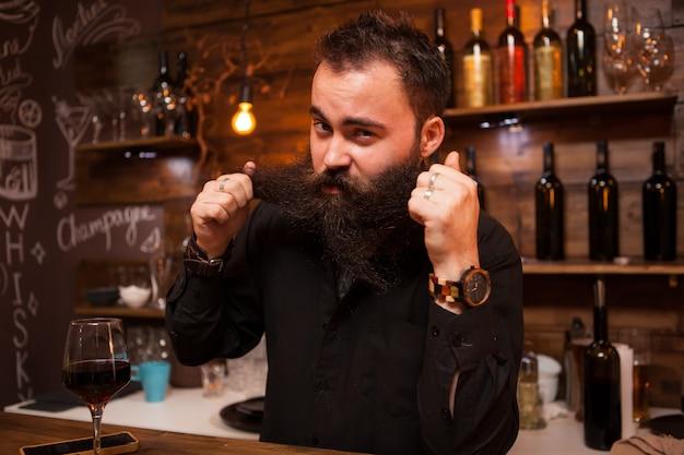 Barista attraente che gioca con la sua lunga barba dietro il bancone. uomo alla moda.
