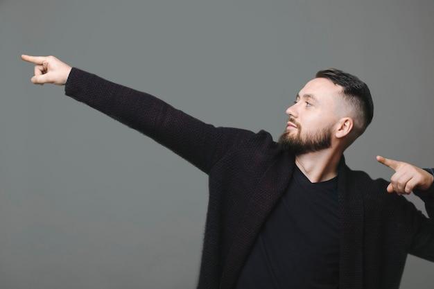 Attraente ragazzo barbuto in giacca elegante che guarda lontano e che indica da parte con entrambe le mani mentre si trova su sfondo grigio