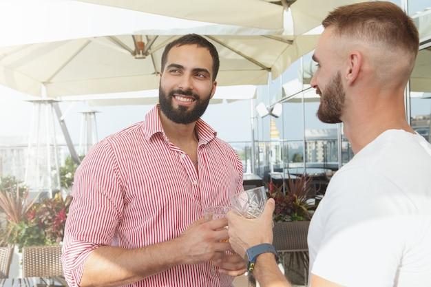 Attraente uomo barbuto che beve whisky con il suo amico a una festa sul tetto