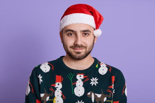 Ragazzo attraente uomo barbuto con buon umore abiti maglione divertente e cappello rosso della santa sulla viola