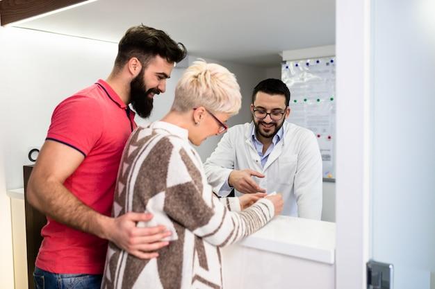 Uomo barbuto attraente con sua moglie incinta che ha cure mediche in studio dentistico.