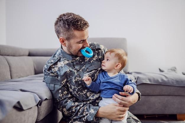 Attraente soldato barbuto seduto sul pavimento in soggiorno, tenendo il suo amato adorabile bambino, tenendo il massaggiagengive in bocca e stuzzicandolo.
