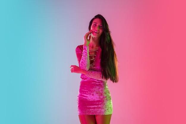 Attraente. bella ragazza seducente in abito alla moda, vestito su sfondo rosa-blu sfumato alla luce al neon. ritratto a mezzo busto. copyspace per l'annuncio. estate, moda, bellezza, concetto di emozioni.