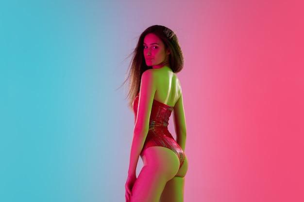 Attraente. bella ragazza seducente in costume da bagno rosso alla moda su sfondo rosa-blu sfumato alla luce al neon. ritratto a mezzo busto. copyspace per l'annuncio. estate, moda, bellezza, concetto di emozioni.