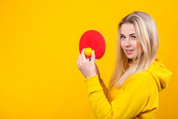 La bella giovane donna bionda attraente in vestiti sportivi gialli casuali gioca a ping-pong, tenendo una palla e una racchetta.