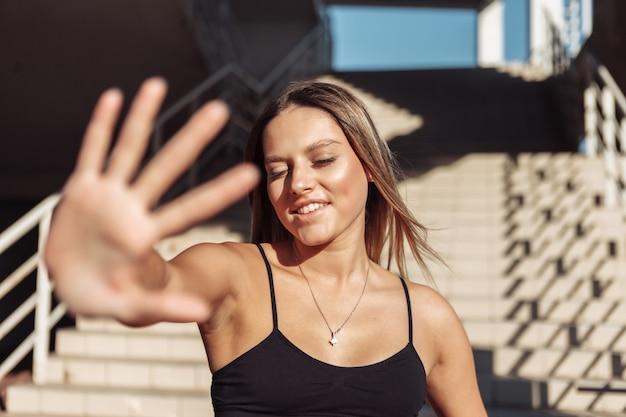 Attraente modello di fitness di bellezza in posa al sole del mattino sullo sfondo dei gradini