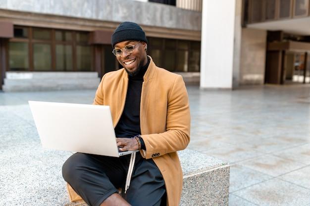 Attraente uomo barbuto nero in abiti eleganti seduto utilizzando computer portatile sorridente con faccia positiva. stile di vita urbano.