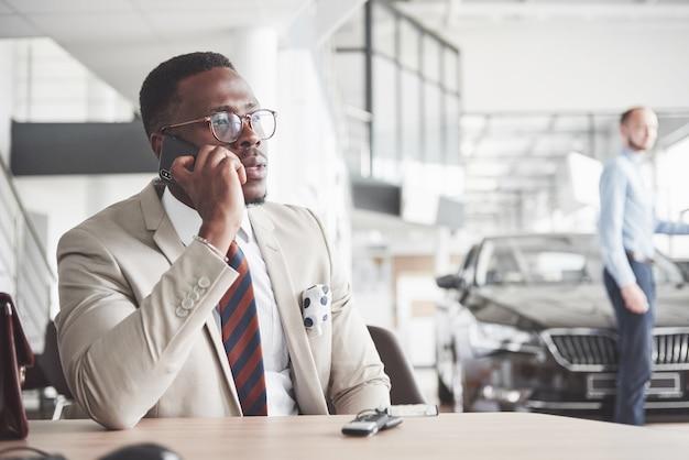 Attraente uomo d'affari nero si siede al tavolo della concessionaria auto, firma un contratto e acquista una nuova auto.