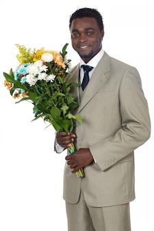 Attraente uomo nero con un mazzo di fiori