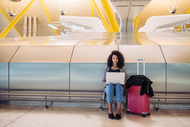 Donna di colore attraente all'aeroporto che si siede e che lavora con il computer portatile