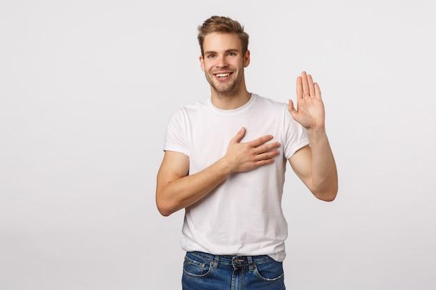 Attraente uomo biondo con la barba in maglietta bianca solleva una mano e ne tiene un'altra sul cuore