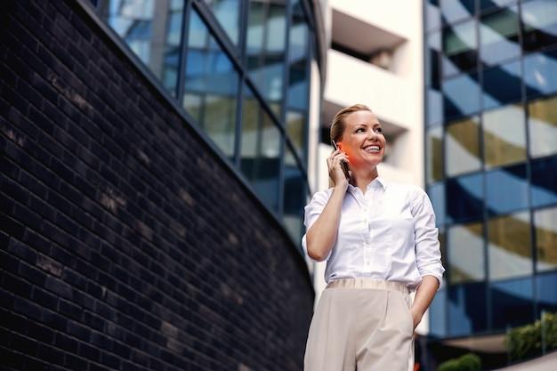 Attraente bionda alla moda imprenditrice parlando al telefono in business center esterno.