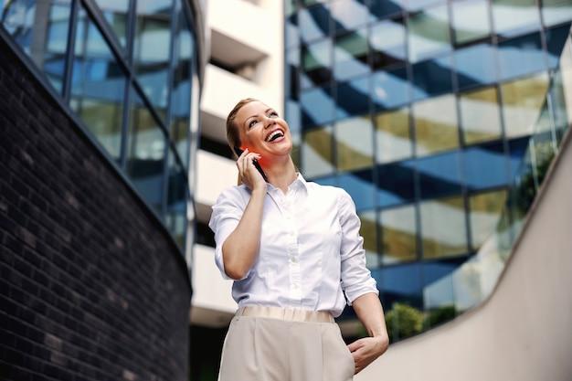 Attraente bionda alla moda imprenditrice parlando al telefono in business center esterno