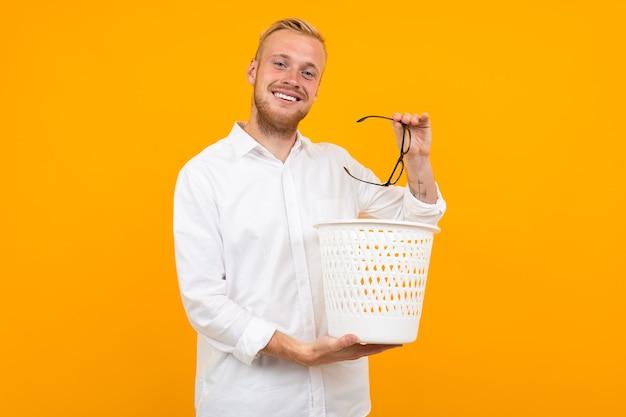 Attraente uomo biondo vestito con una classica camicia bianca getta i bicchieri nel cestino della spazzatura su uno sfondo giallo.