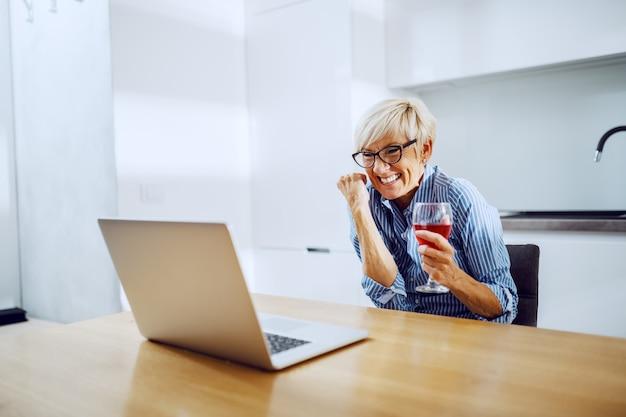 Donna senior bionda attraente che si siede al tavolo da pranzo, bevendo vino, esaminando computer portatile e incoraggiando il successo