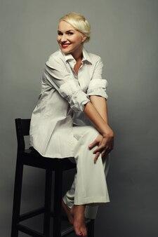 Attraente donna bionda su sfondo grigio