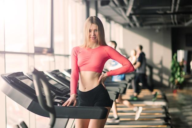 Attraente femmina caucasica bionda in esecuzione sul tapis roulant in palestra durante e dopo l'allenamento