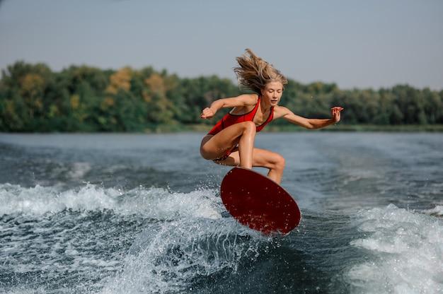 Ragazza bionda attraente che salta sul wakeboard rosso