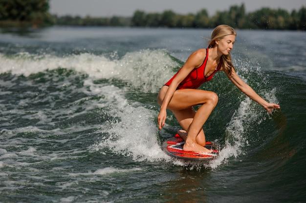 Ragazza bionda attraente che guida sul wakeboard rosso