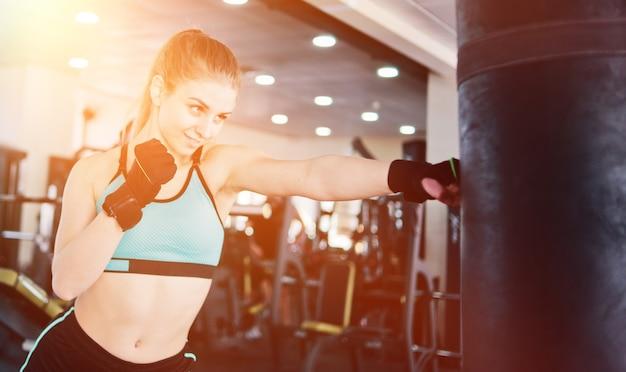 Attraente donna bionda boxe e allenamento il suo pugno con sacco da boxe in palestra