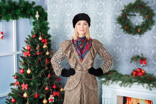 Attraente donna bionda in un vestito marrone e un cappello di pelliccia nero vicino all'albero di natale e camino