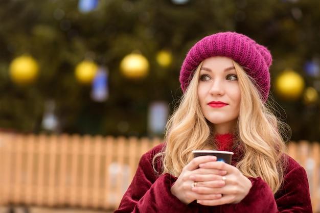 Attraente donna bionda che beve caffè vicino all'albero di natale nella piazza centrale di kiev