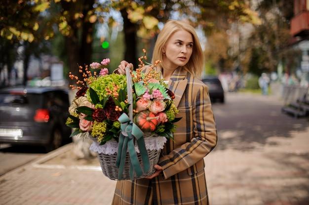 Donna bionda attraente che tiene un grande cestino di vimini dei fiori contro la città