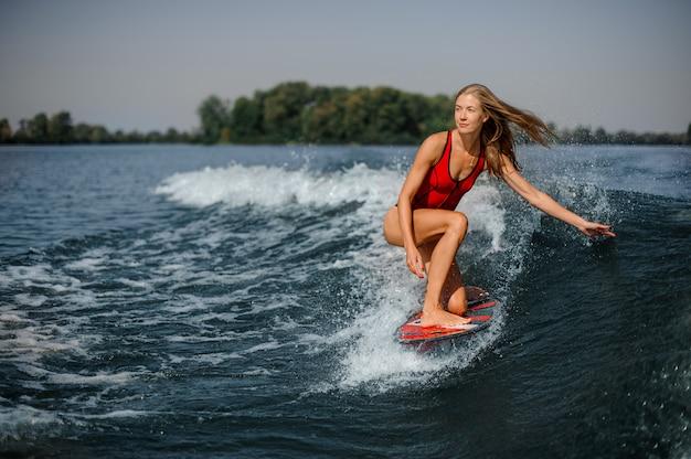 Surfista biondo attraente della donna che guida giù l'onda di spruzzatura blu