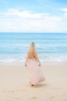 Attraente giovane donna bionda si trova sulla sabbia bianca
