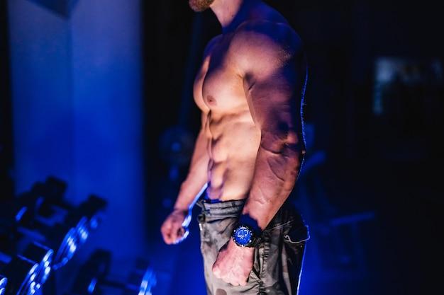 Body builder attraente in posa e mostra i muscoli su nero e blu scuro.