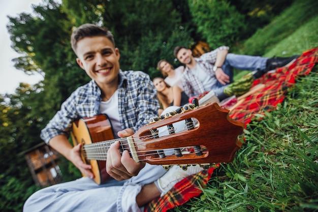 Ragazzo attraente seduto in erba e suonare la chitarra, ha un picnic con tre amici.