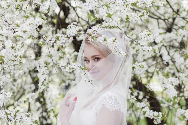 Una sposa attraente in un abito di pizzo e un velo sorride vicino agli alberi in fiore nel parco