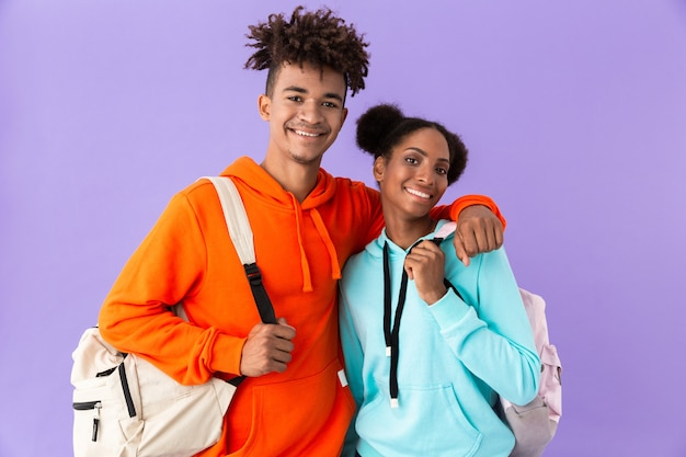 Attraente fratello e sorella che indossano zaini che abbracciano insieme, isolato sopra la parete viola