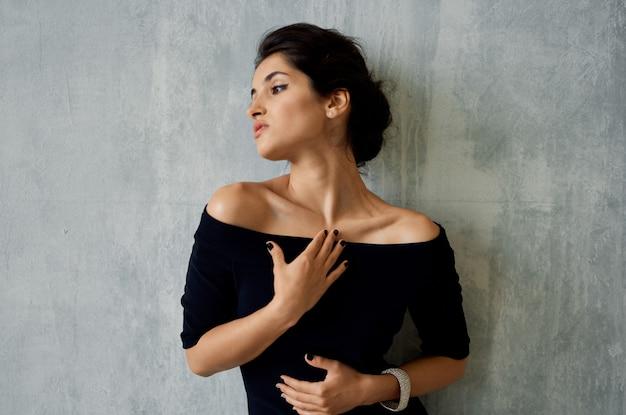Attraente bruna in posa nera per il trucco della decorazione del vestito da sera