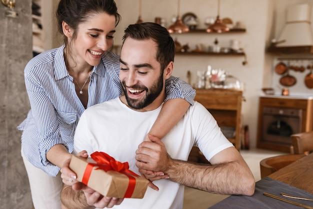 Attraente brunetta coppia uomo e donna facendo colazione in appartamento mentre era seduto al tavolo con la presente casella