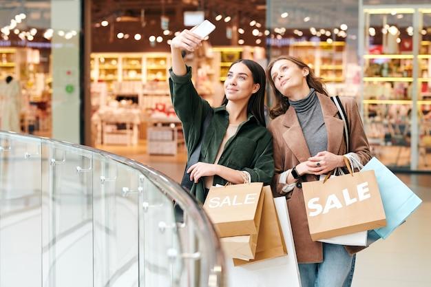 Attraente ragazza bruna in camicia di velluto che tiene le borse della spesa e fotografare con un amico nel centro commerciale