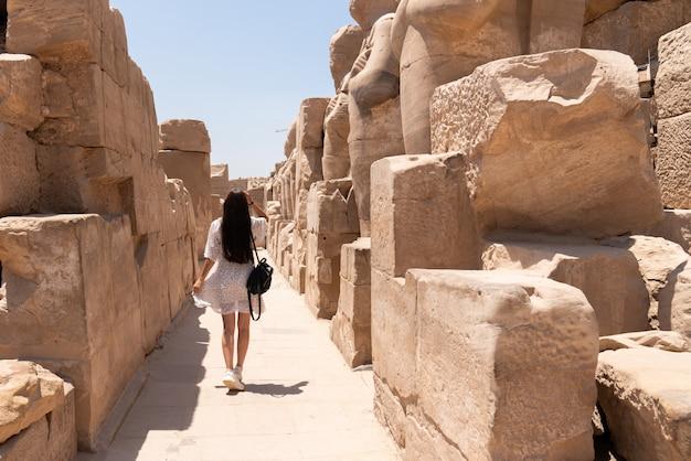 Attraente ragazza bruna in abito bianco cammina tra le antiche rovine del tempio di karnak a luxor. egitto