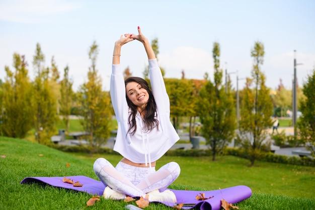 Attraente ragazza bruna in abbigliamento sportivo bianco si siede su un tappetino viola nella posa del loto e allunga le mani sotto la testa, fitness all'aperto, esercizi di yoga