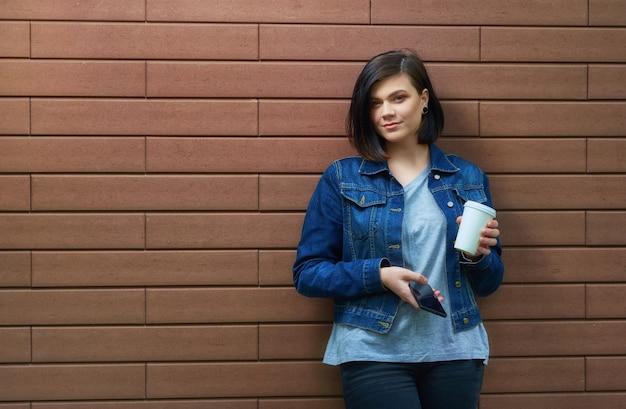 Attraente ragazza bruna con tunnel nelle orecchie in una giacca di jeans blu con una tazza di caffè e smartphone in piedi davanti al muro di mattoni.