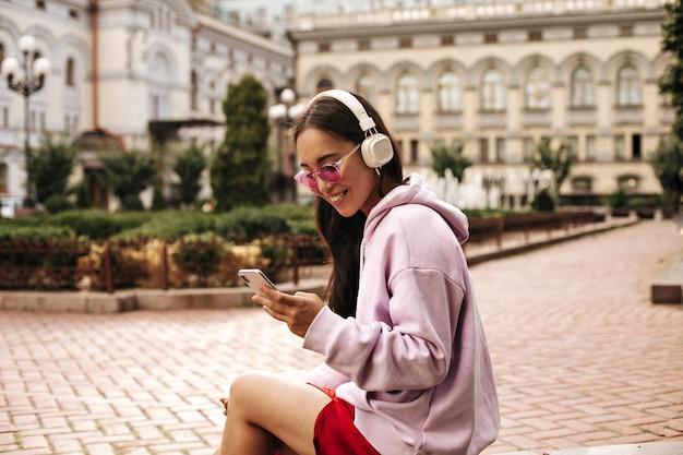 Attraente signora bruna in cuffia ascolta musica