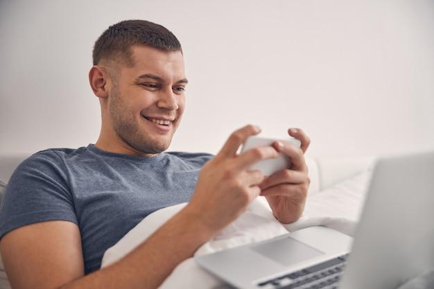 Attraente maschio bruna che ride mentre lavora online a letto e allo stesso tempo chiacchiera al telefono