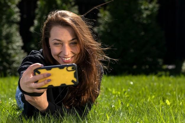 Attraente modella bruna con capelli lunghi vestita in felpa con cappuccio nera sdraiato sul prato verde fa selfie in una bella giornata estiva guardando smartphone