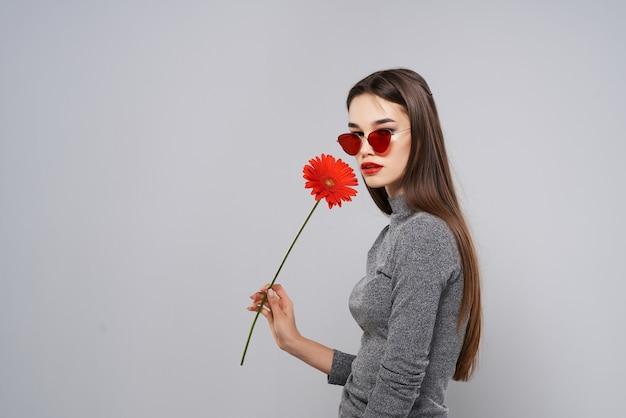 Attraente bruna indossando occhiali da sole trucco romanticismo fiore rosso. foto di alta qualità