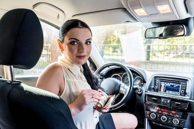 Attraente bruna con un mazzo di dollari all'interno dell'auto