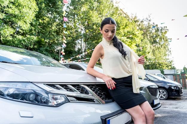 Attraente donna bruna in posa vicino alla nuova auto