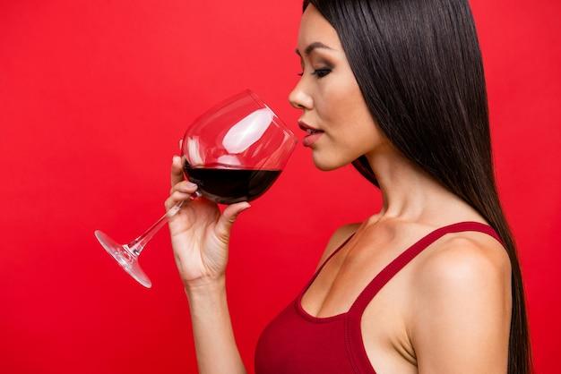 Attraente donna bruna in un abito rosso in posa contro il muro rosso