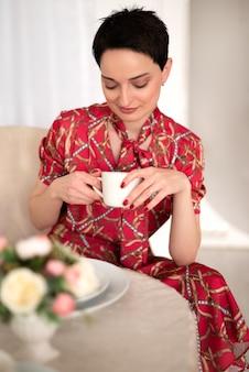 Attraente donna castana in abito rosso si siede al set table e beve il tè dal ritratto del primo piano tazza bianca